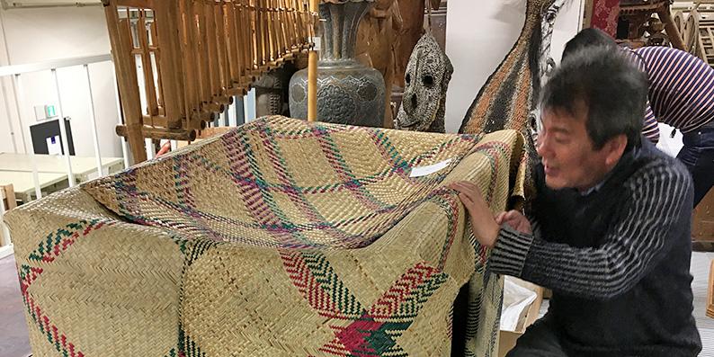 国立民族学博物館の収蔵庫で著者がマダガスカルの新生児・妊婦用寝台にさわって調査しているところ