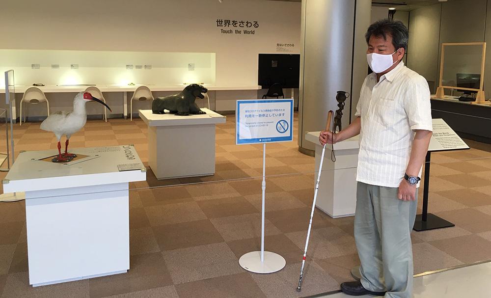 民博の「世界をさわる」コーナーの前に立つ広瀬浩二郎。展示上にはロープが張られ、「新型コロナウイルス感染症の予防のため利用を一時停止しています」という看板が立っている