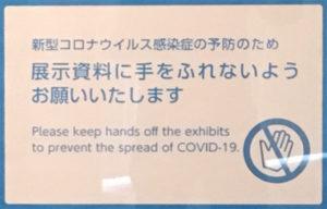 「新型コロナウイルス感染症の予防のため 展示資料に手を触れないようお願いいたします」と書いてある看板
