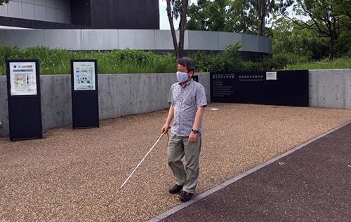 写真:マスク着用で白杖を持ち万博公園内を歩く様子